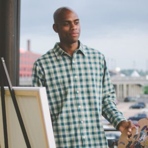 Portrait of Omari Booker standing in front of his easel, overlooking the city.