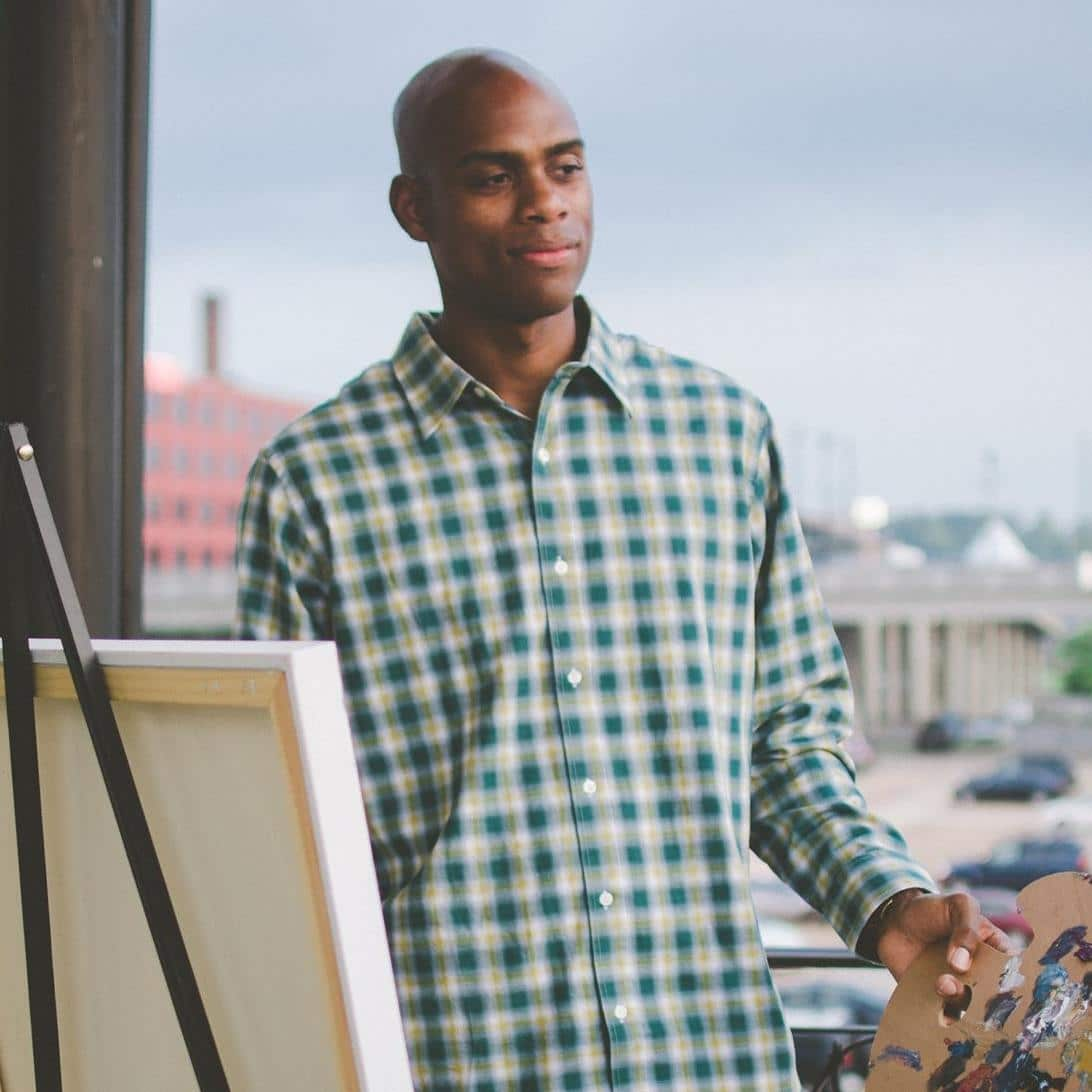 Portrait of Nashville-based painter Omari Booker standing at his easel while holding a painter's palette.