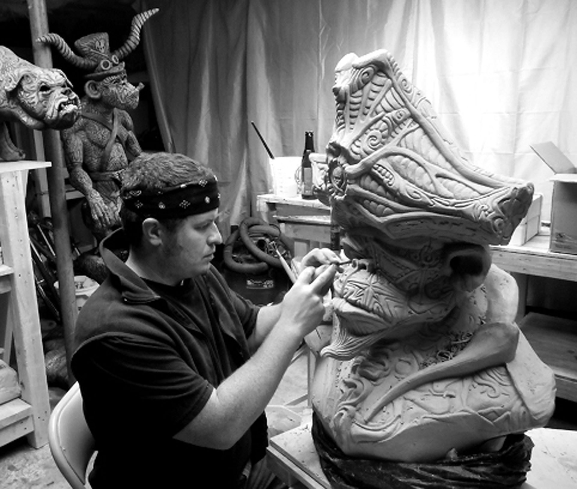 Brian Somerville working on sculpting one of his monsters in his studio.