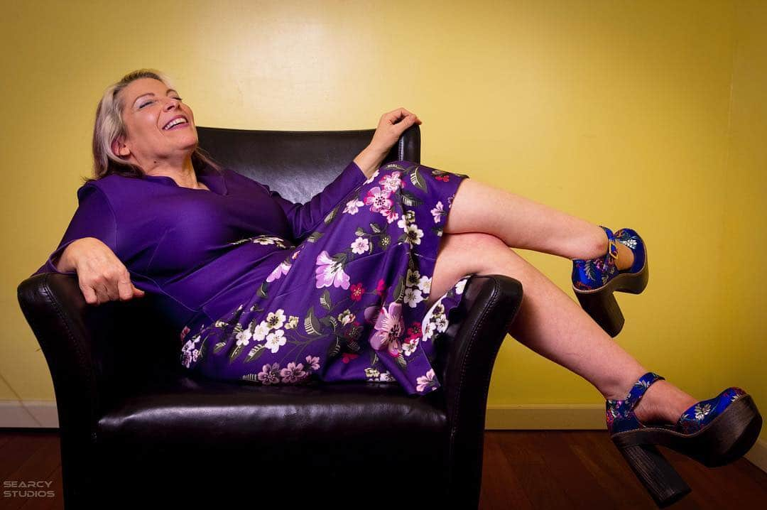 Alicia is lounging in a black leather chair set against a yellow wall. She's wearing a vibrant purple outfit and her feet are dangling over the armrests of the chair.