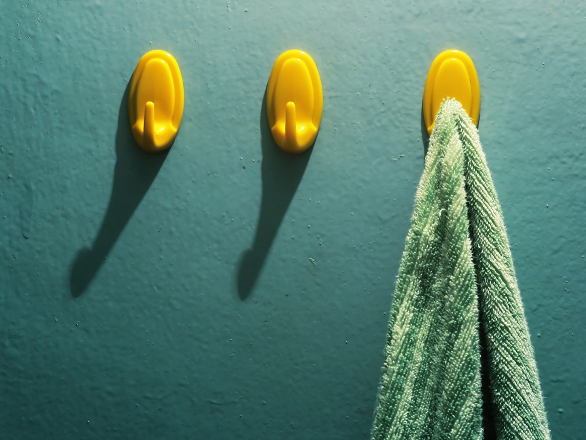 A row of yellow towel hooks on a green wall. A green towel is hanging on the last hook on the right.
