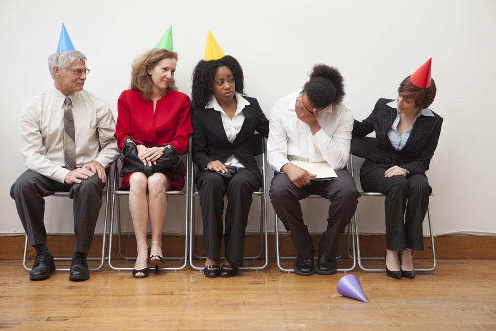 A group of office workers sitting awkwardly by the wall in a party, wearing multi-colored party hats.