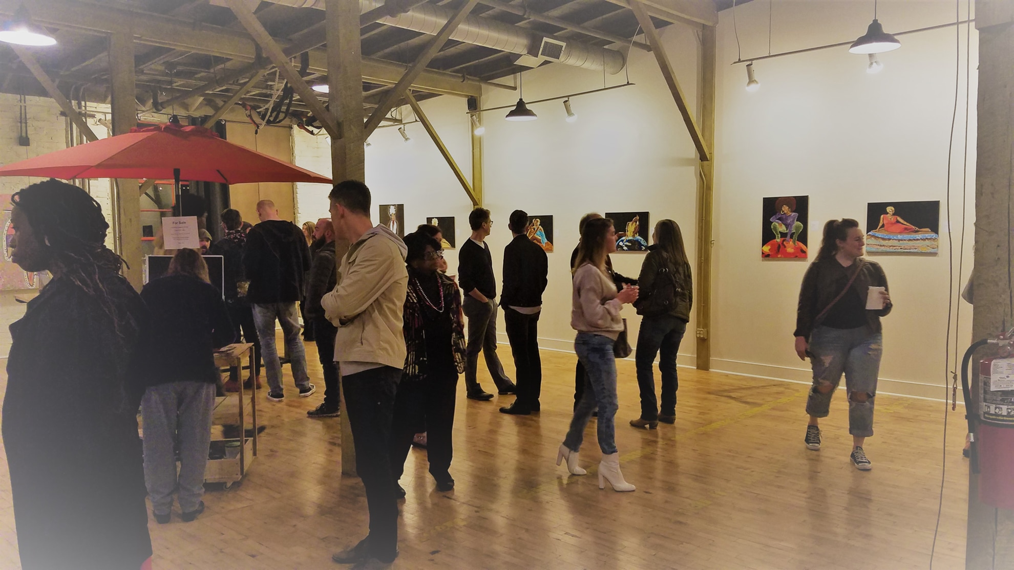 Photo of the opening of the Core Essence by Amanda Downs in abrasiveMedia in February of 2019. A group of people are viewing art on the walls and socializing.