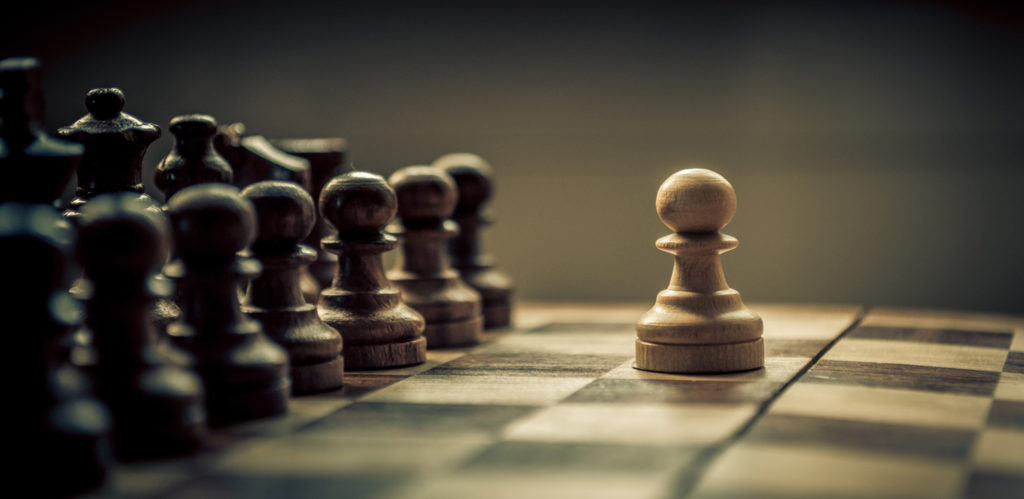 Small chess pawn facing off against a line of opposing chess pieces